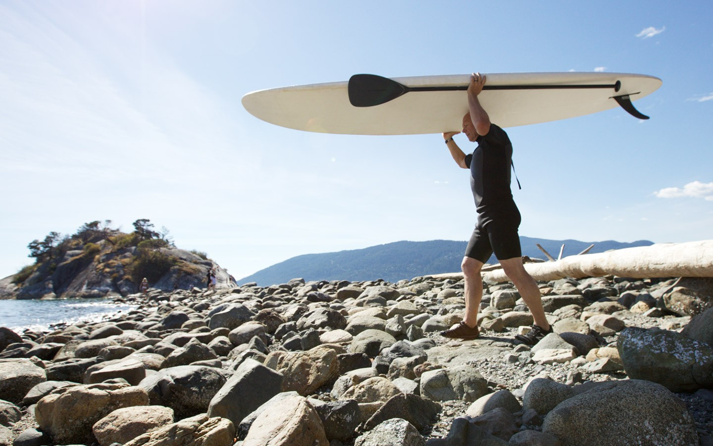 Mature adult carrying paddle board across the beach towards the sea.